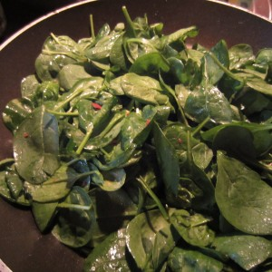 Fresh spinach in olive cook with turkey bacon bits.
