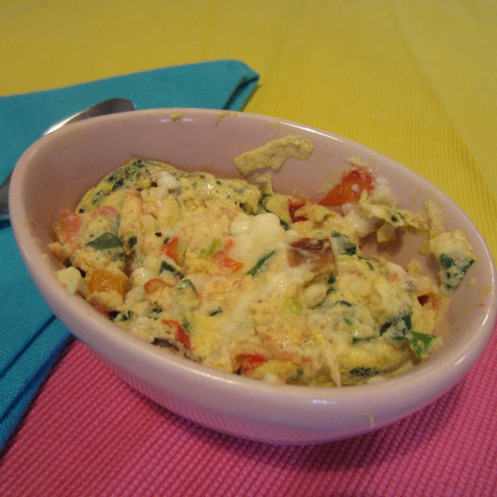 Cheesy egg scramble in an egg shaped dish.