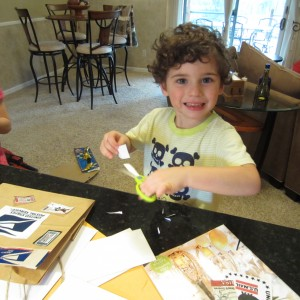 My three-year old grandson cutting out his postage stamps.