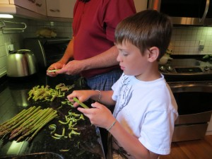 Carson helps Poppy peel the asparagus for grilling.