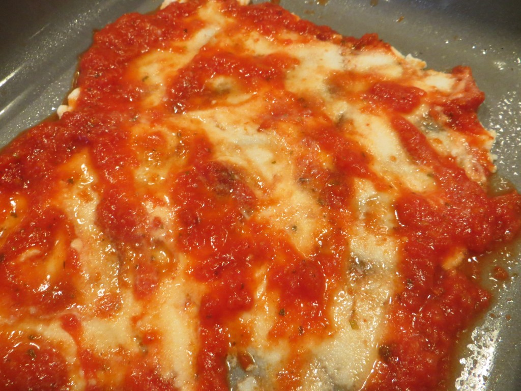 Spread the marinara sauce over the stuffed shells.